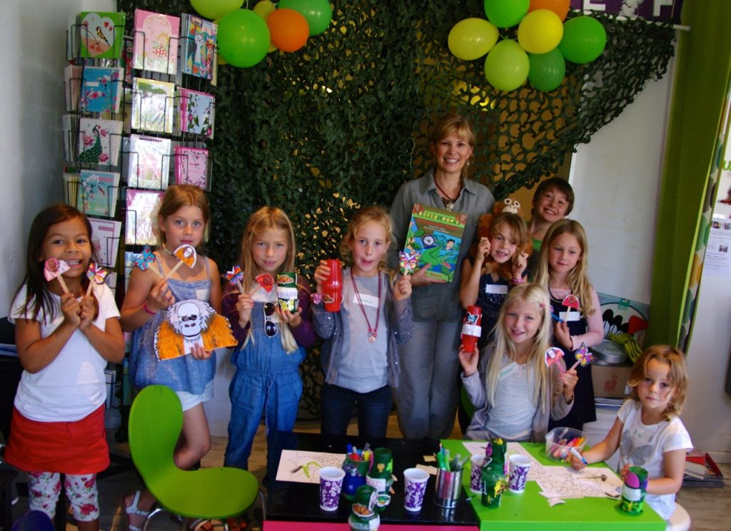 Author Sandra Arthur with her book and a group of children