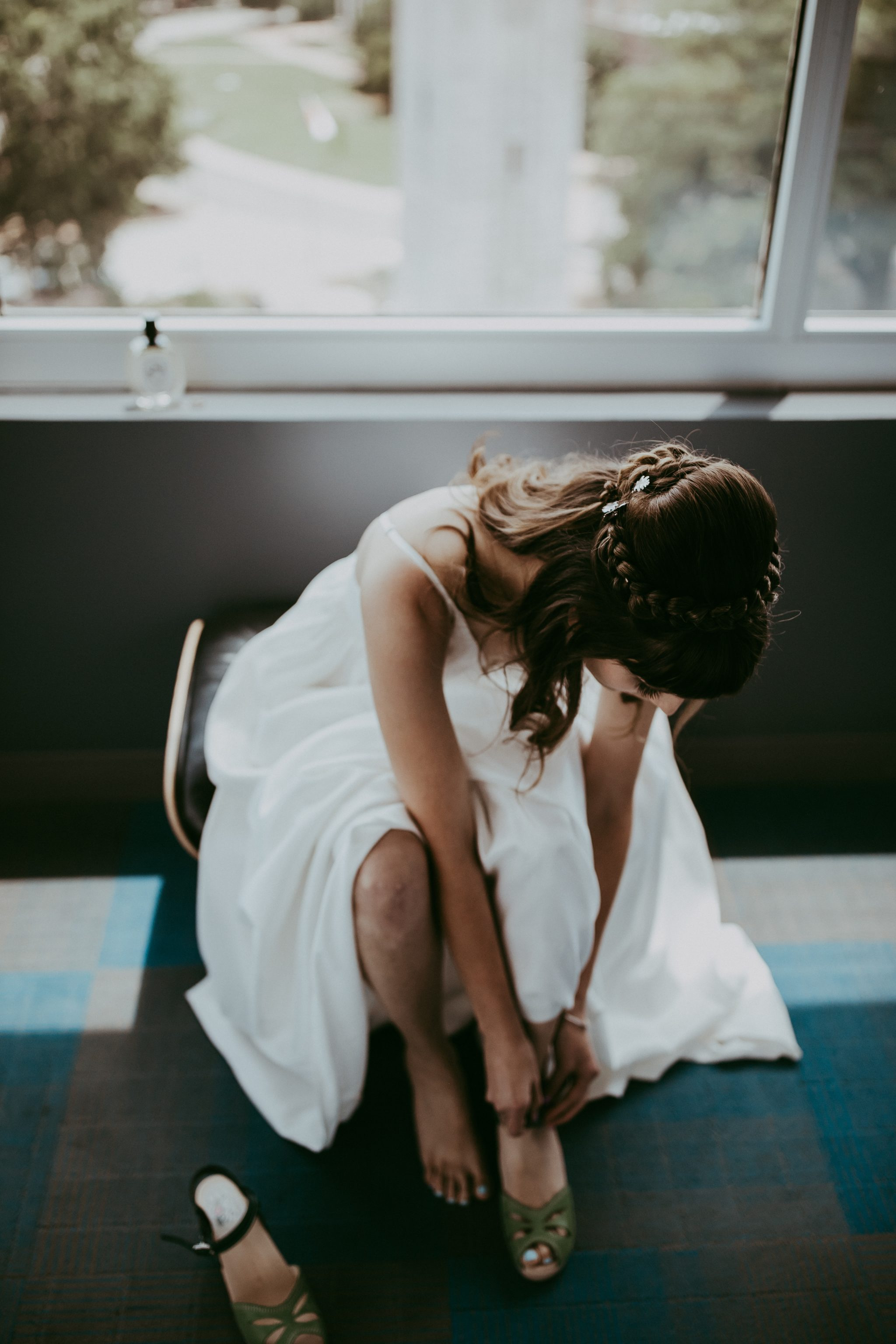 Bride sits in chair wearing sustainable wedding dress from Fame & Partners and puts on handmade clogs by Maguba.