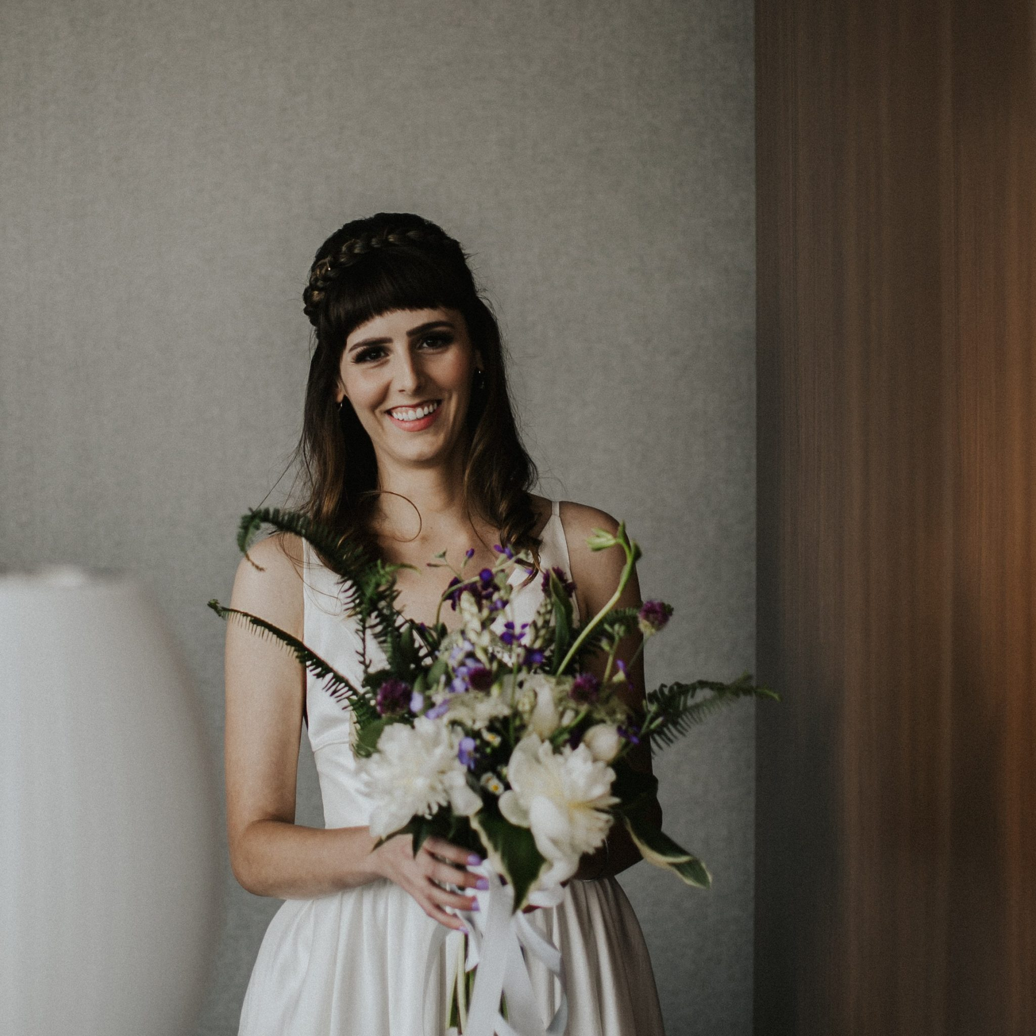 Southern bride holds DIY bridal bouquet made from local, seasonal flowers.