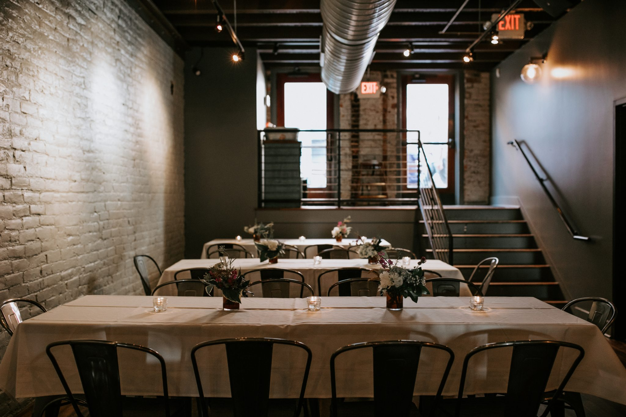Three rows of minimalist wedding reception tables with simple DIY floral arrangements, candles, and white linens.