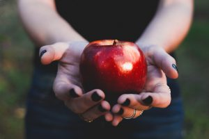 Woman holding red apple with black fingernail polish and rings. Photo by Thammie Cascales on Unsplash